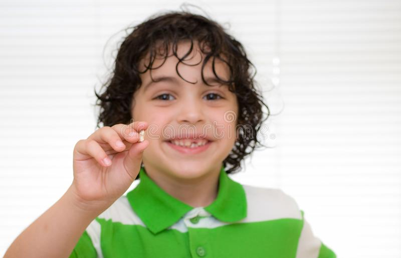 Child showing a milk tooth and smiling royalty free stock photos