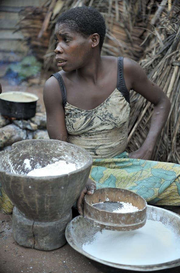 Dschungel des AUTOS afrika Dschungel der Republik Zentralafrika Baka-Frau kocht das Lebensmittel und zerquetscht ein Mehl in eine stockfotografie