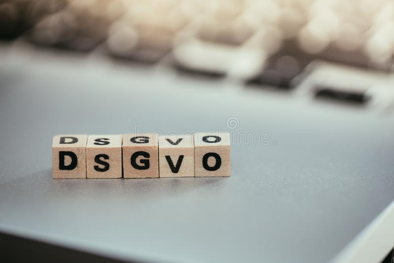 """DSGVO: Wooden cubes with letters """"DSGVO"""" lying on a laptop. Datenschutzgrundverordnung royalty free stock image"""