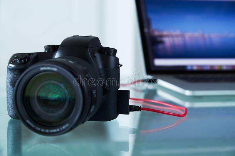 DSLR照片照相机被束缚对有USB缆绳的便携式计算机 图库摄影