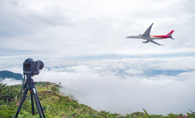 DSLR-camera die de fotografie van de reisaard nemen de volledige kadercamera op driepoot neemt foto van vliegtuigstart met mooie  stock fotografie