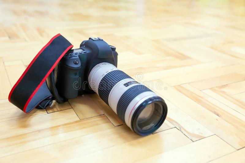 DSLR Camera with telephoto lens is on the parquet floor. DSLR Camera with telephoto lens is on the wooden parquet floor royalty free stock image