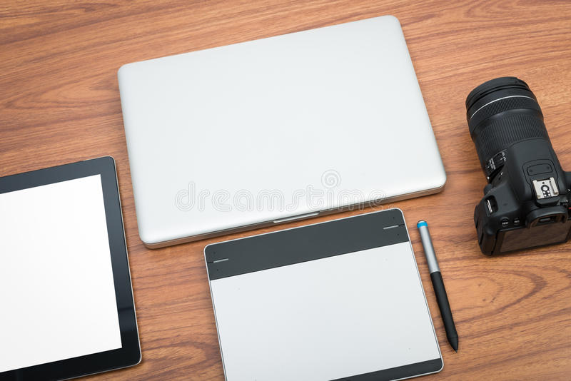 DSLR digital camera with tablet and notebook laptop stock image