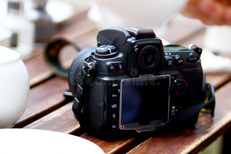 DSLR-Fotokamera, die auf Tabelle steht stockfotografie