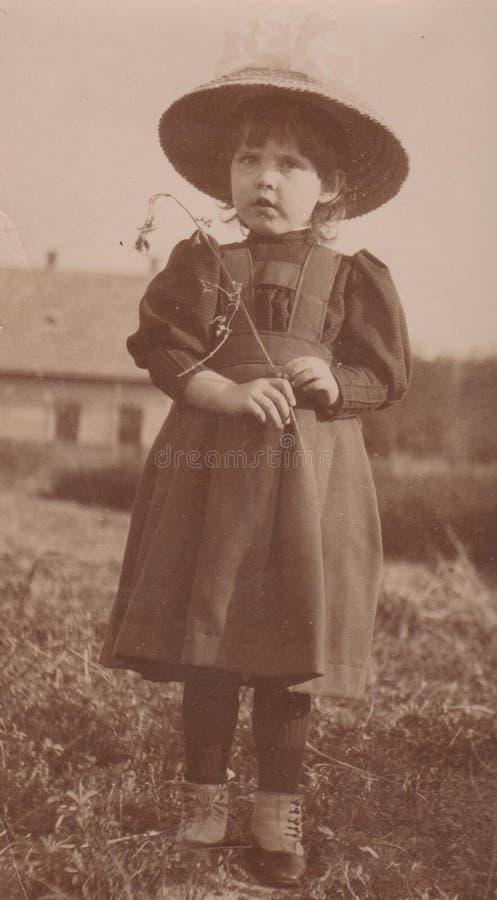 DT00003 ΟΥΓΓΑΡΙΑ CIRCA 1910 - όμορφη λίγο κορίτσι χωρών με το μεγάλο καπέλο εξετάζει περίεργα τη κάμερα austro-Ουγγαρία στοκ εικόνες