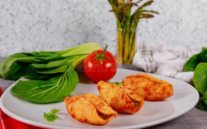 Duże makaron skorupy obsdzać personelem z mięsem, serem i pomidorowym kumberlandem, zdjęcie royalty free