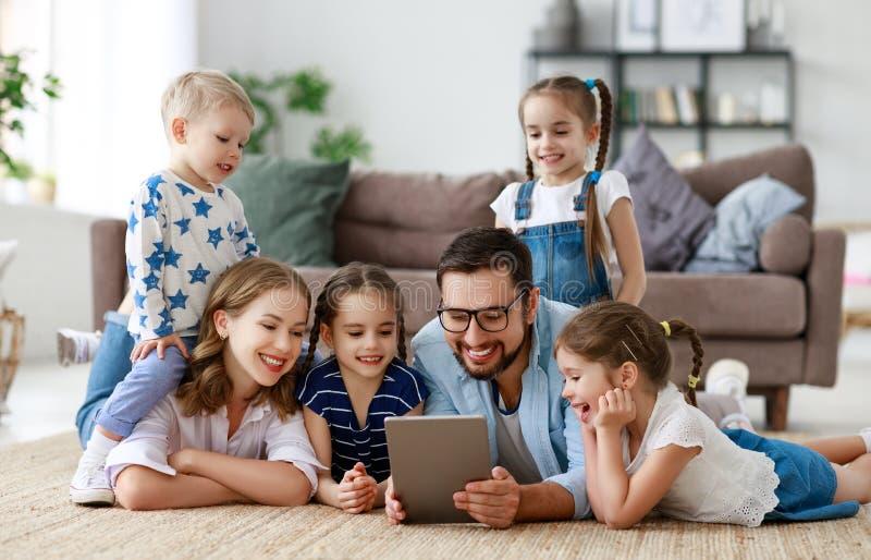 Dużej rodziny matka, ojciec i dzieci z pastylka komputerem, w domu obraz royalty free