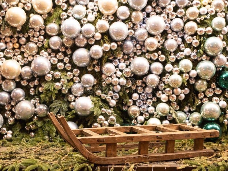 Duży pusty sanie z ogromnymi błyszczącymi szklanymi dekoracyjnymi srebnymi kolor piłkami zakrywał całkowitą ścianę na tle fotografia stock