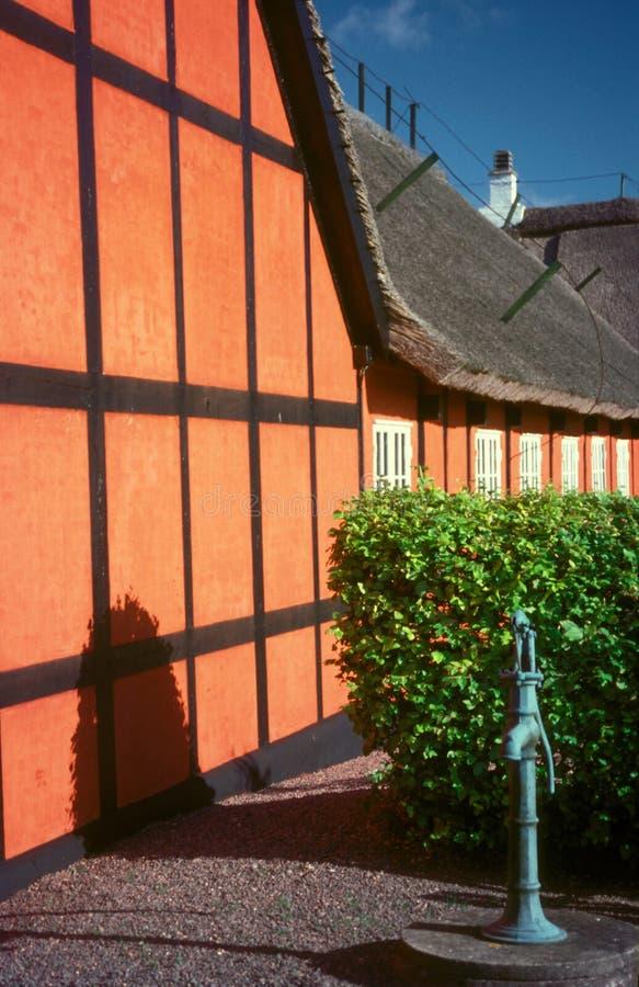 Duńska czerwień cembrujący dom z starą pompą wodną zdjęcie royalty free