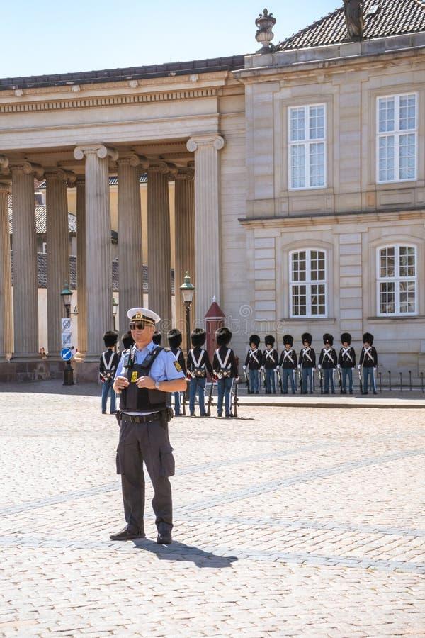 Duński policjant patrzeje dla rozkazu blisko do Królewskiego Amalienborg pałac strażnika w duńskim kapitale Kopenhaga zdjęcie royalty free