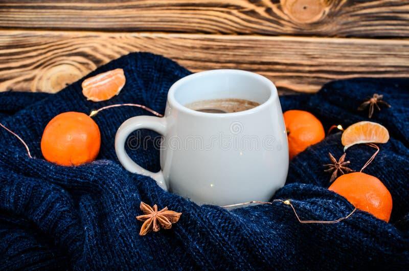 Duża biała filiżanka kakao na błękitnym trykotowym pulowerze z wibrującymi pomarańczowymi tangerines wokoło i anyży ziarnami przy fotografia royalty free
