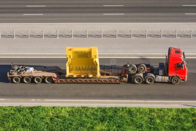 Duża ciężarówka z depresji estradową przyczepą niesie a z wielkimi częściami dla przemysłowych maszyn zdjęcia stock