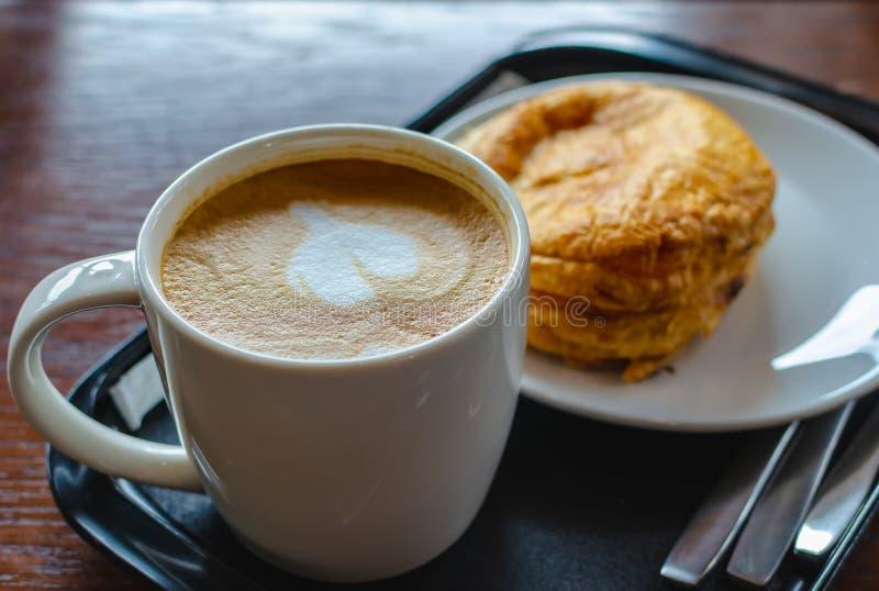 Duża filiżanka gorąca kawa z croissant w sklep z kawą fotografia royalty free