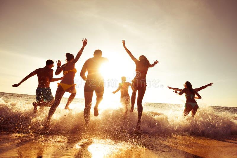 Duża firma przyjaciele ma zabawę przy zmierzch plażą zdjęcia stock