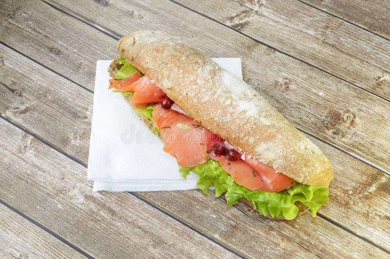 Duża i serdecznie kanapka z, łososiem polędwicowym, sałatkowym, pojęcie lunch na drewnianym stojaku fotografia stock