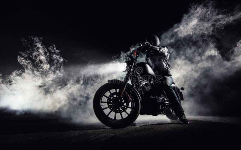 Duża moc motocyklu siekacz z mężczyzna jeźdzem przy nocą zdjęcie stock