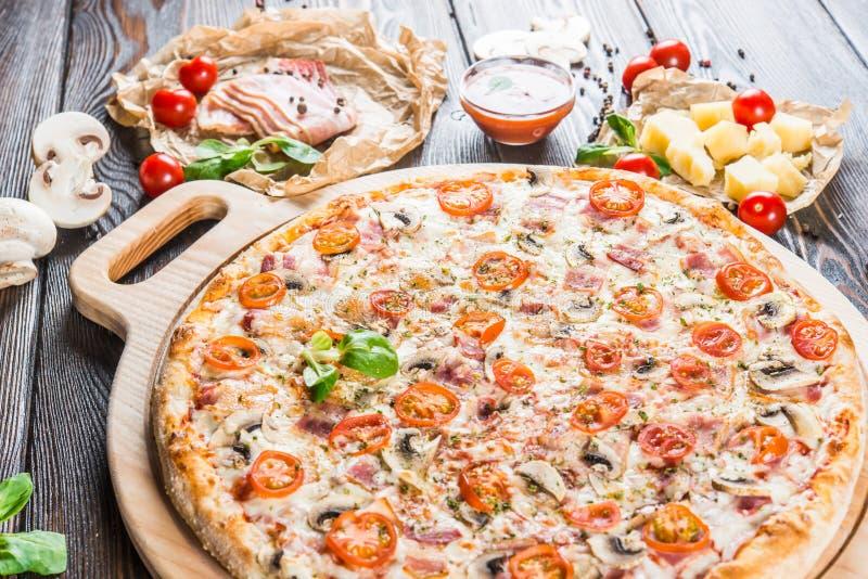 Duża pizza z baleronem i ananasem na round tnącej desce na d zdjęcia stock