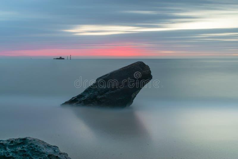 Duża skała przy plażą z marzycielskim zmierzchem zdjęcie royalty free