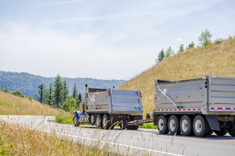 Duża takielunek porady ciężarówka z dwa usyp przyczepami jedzie na wijącej drodze między wzgórzami obrazy royalty free