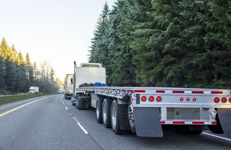 Duża takielunku dalekiego zasięgu ciężarówka z pustym płaskiego łóżka przyczepy bieg na zimy drodze w konwoju z inny semi semi se obraz stock