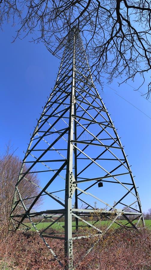 Duża władza pilonu odtransportowania elektryczność w wieś terenie fotografia stock