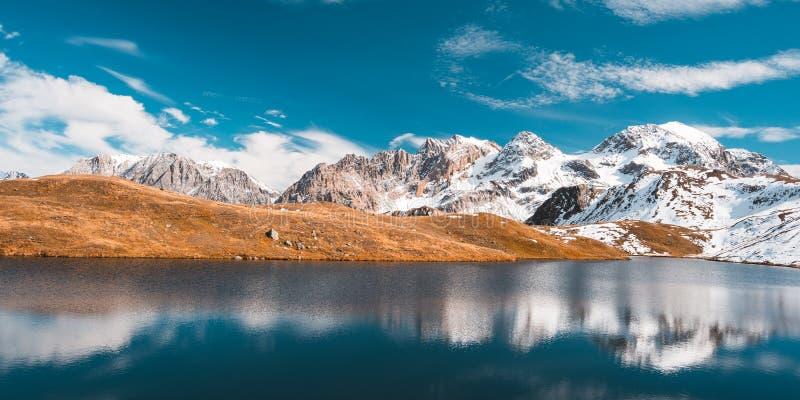 Duża wysokość wysokogórski jezioro w idyllicznej ziemi z odbiciem majestatyczni skaliści halni szczyty Szeroki kąta widok na Alps zdjęcie stock