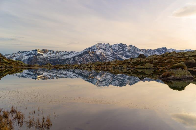 Duża wysokość wysokogórski jezioro w idyllicznym krajobrazie Odbicie snowcapped pasmo górskie i sceniczny kolorowy niebo przy zmi zdjęcia royalty free