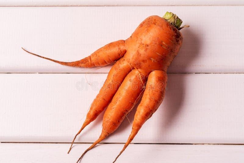 Duże brzydkie wyginać się marchewki na białym drewnianym tle zdjęcia stock