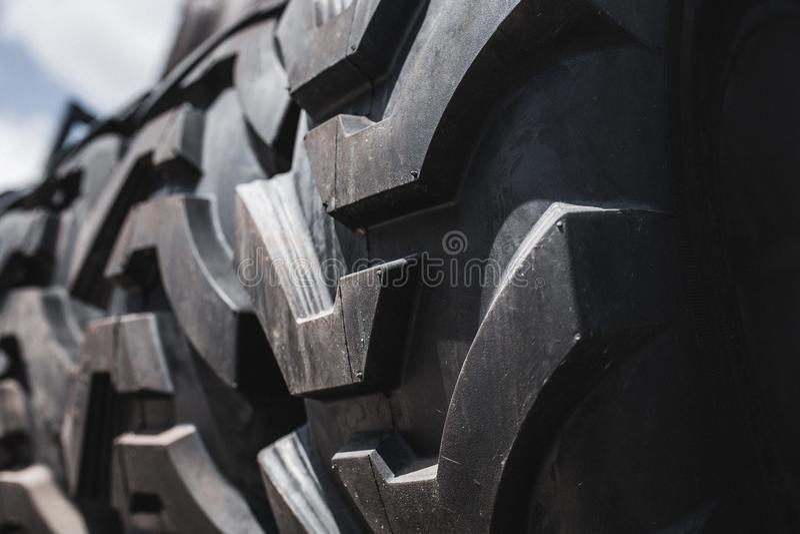 Duże czarne ogromne duże ciężarówki, ciągnika lub buldożeru ładowacza opony, toczą w górę stojaka, sklepowych sprzedawanie opon d zdjęcie royalty free