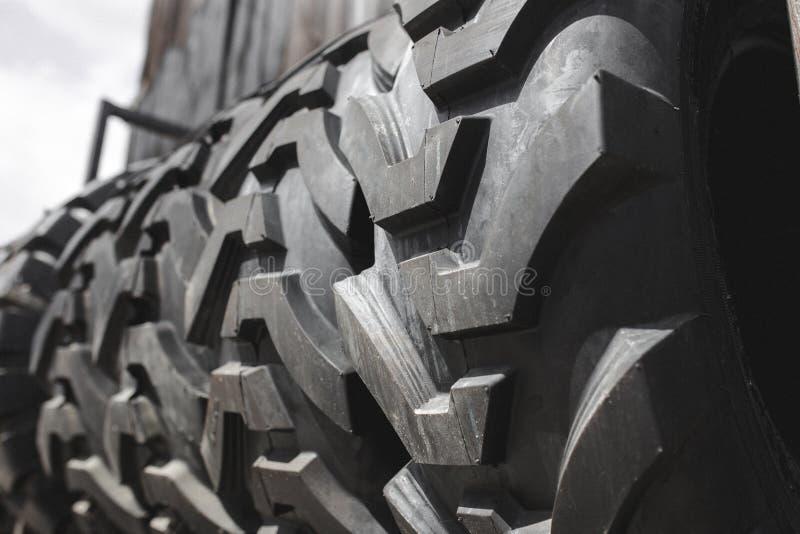 Duże czarne ogromne duże ciężarówki, ciągnika lub buldożeru ładowacza opony, toczą w górę stojaka, sklepowych sprzedawanie opon d zdjęcia royalty free