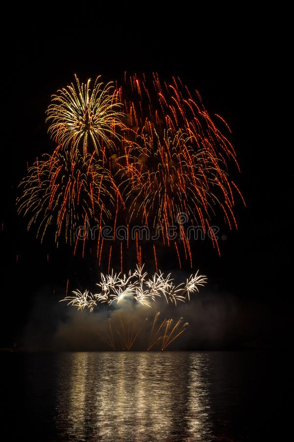 Duże i bogate gwiazdy z chrupotanie skutkiem od fajerwerków nad Brno tamą z jeziornym odbiciem pomarańcze i koloru żółtego fotografia stock
