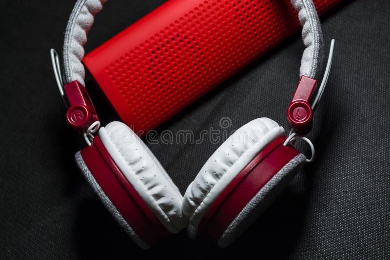 Duże słuchawki biali i czerwoni kolory Mały przenośni mówcy Czarny tło Nowożytna mobilna elektronika gadżety zdjęcia stock