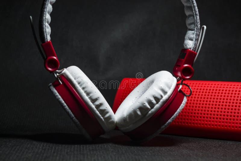 Duże słuchawki biali i czerwoni kolory Mały przenośni mówcy Czarny tło Nowożytna mobilna elektronika gadżety zdjęcia royalty free