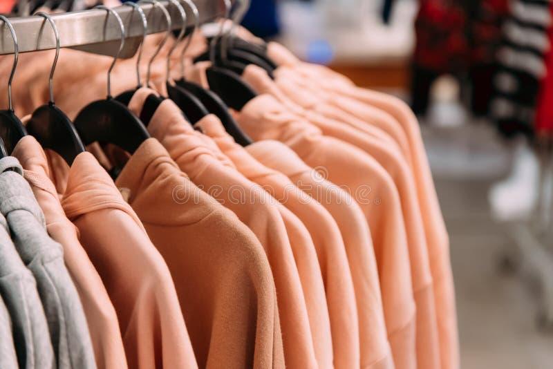 Dużo Colour Okapturzali bluzę sportowa Na wieszaku W sklepie zakupy zdjęcia stock