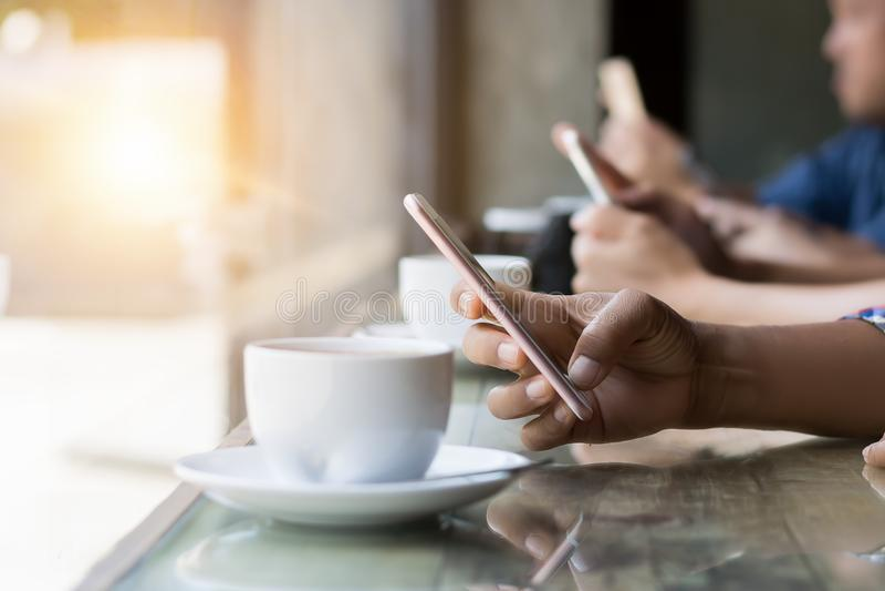 Dużo wręczają używać smartphone w sklep z kawą zdjęcie stock