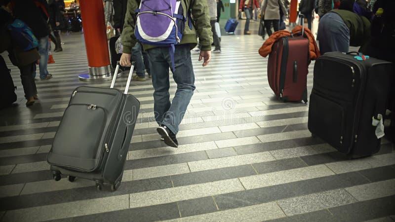 Dużo zaludniają odprowadzenie z bagażem, ruchliwie pasażery przy lotniskiem lub obrazy stock