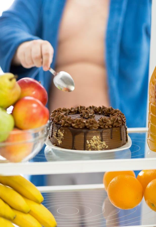 Duży atrakcyjny czekoladowy tort w chłodziarce jest wyzwaniem dla m obraz royalty free