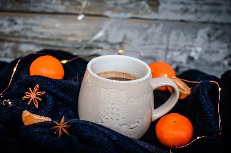 Duży biały kubek z anyżem i tangerines na drewnianym szarym tle Wygodnej zimy domowa atmosfera fotografia royalty free
