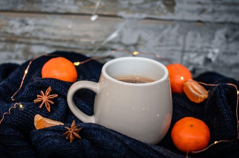 Duży biały kubek z anyżem i tangerines na drewnianym szarym tle Wygodnej zimy domowa atmosfera zdjęcie royalty free