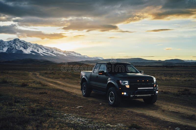 Duży czarny matt Amerykański furgonetka ptak drapieżny jedzie na Kurai stepie przy zmierzchem Lodowowie i Altai góry w tle obrazy royalty free