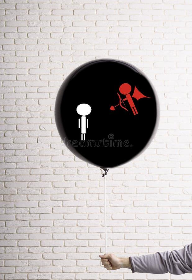 Duży czerń balon w ręce na którym rysują amorek z strzałą i łękiem Walentynki ` s dnia pojęcie obrazy stock