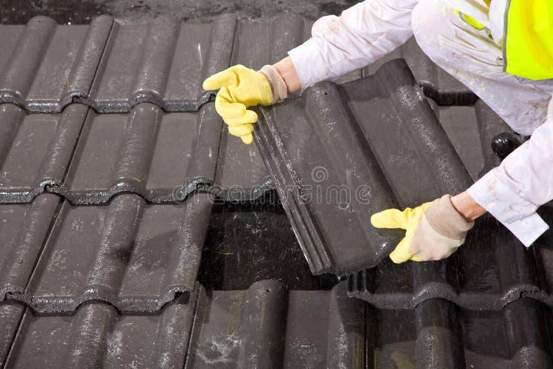 Pracownik na dachowego naprawiania dachowych płytkach obraz royalty free