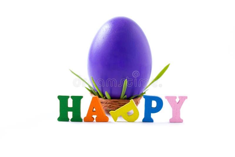 Duży, fiołkowy, kurczak jajko w małym gniazdeczku, i szczęśliwy słowo fotografia stock