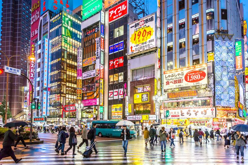 Duży grupa ludzi odprowadzenie wokoło bardzo jaskrawego i colourful terenu Tokio w mokrym dniu w Japonia Tokio, Japonia, Sep - 28 zdjęcie stock