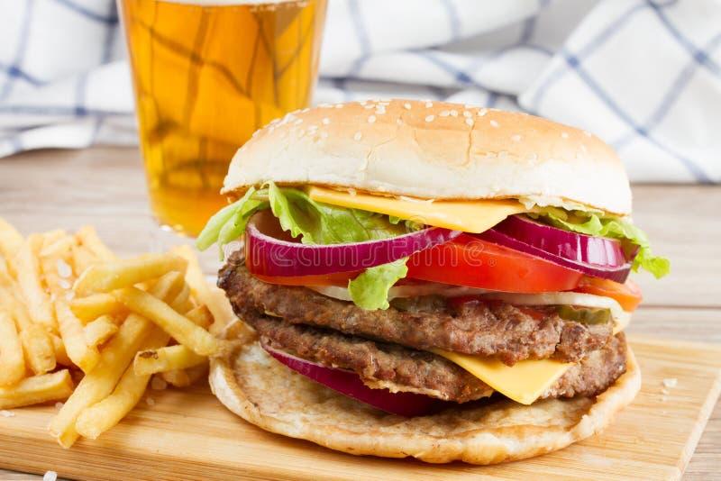 Duży hamburger z francuza piwem i dłoniakami zdjęcie stock