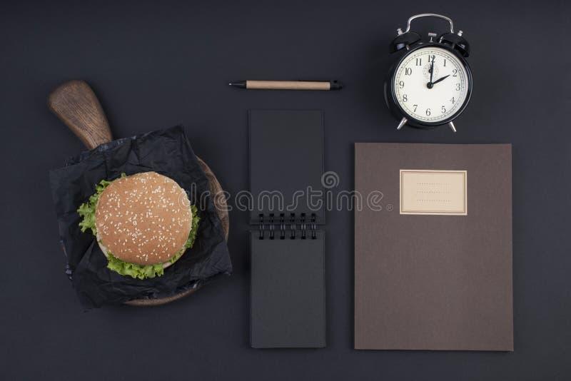 Duży hamburger z sezamowymi ziarnami na czarnym tle Fast food i bezpłatna przestrzeń dla teksta Notepad i notatnik dla rejestrów  zdjęcie stock