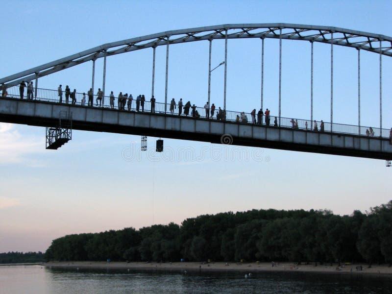 Duży most nad piękną rzeką z ludźmi sylwetek fotografia stock