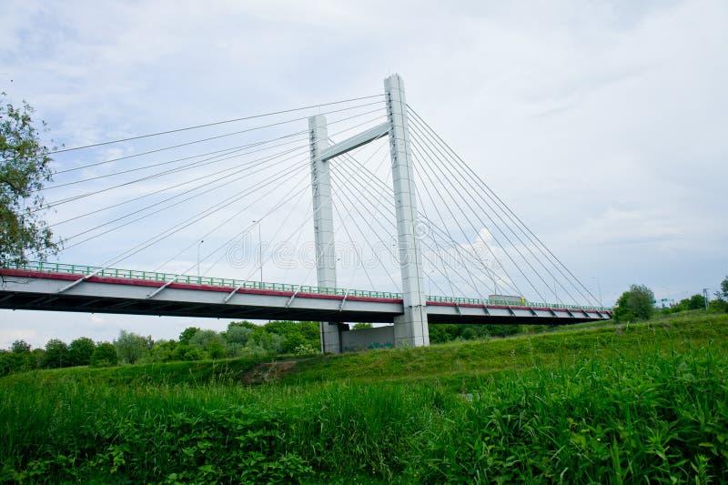 Duży przystojny zostający bridżowy nad rzeką przeciw niebu obraz stock