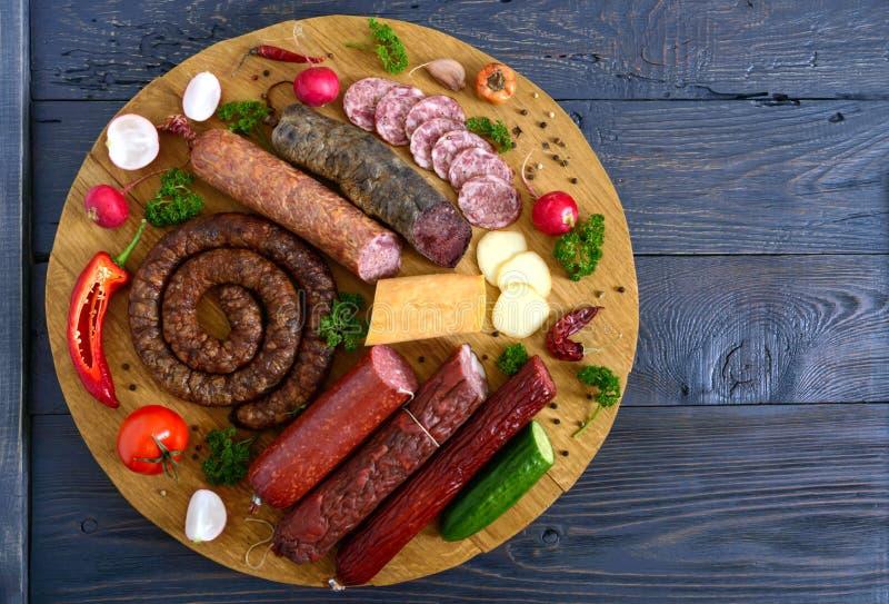 Duży set z kiełbasami Wiele rodzaje kiełbasa, uwędzony ser, świezi warzywa na drewnianej tacy Produkty wakacje zdjęcie royalty free