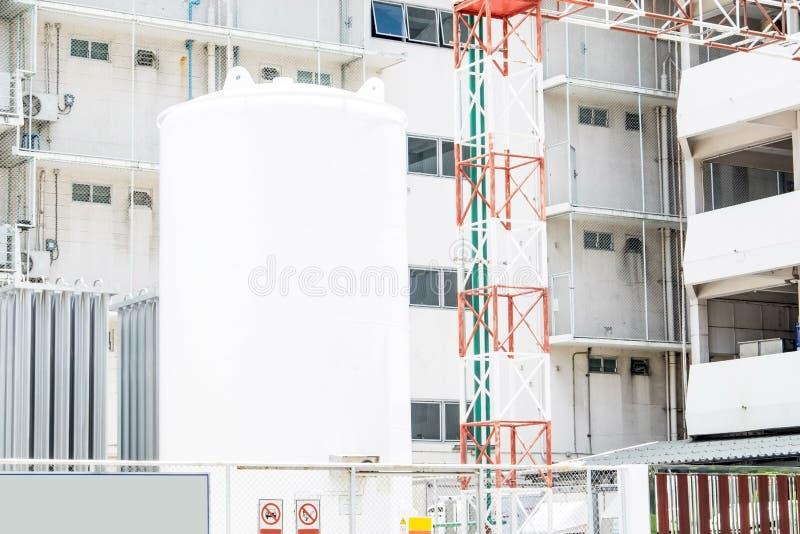 Duży Składowy zbiornik przy budynkiem fotografia stock